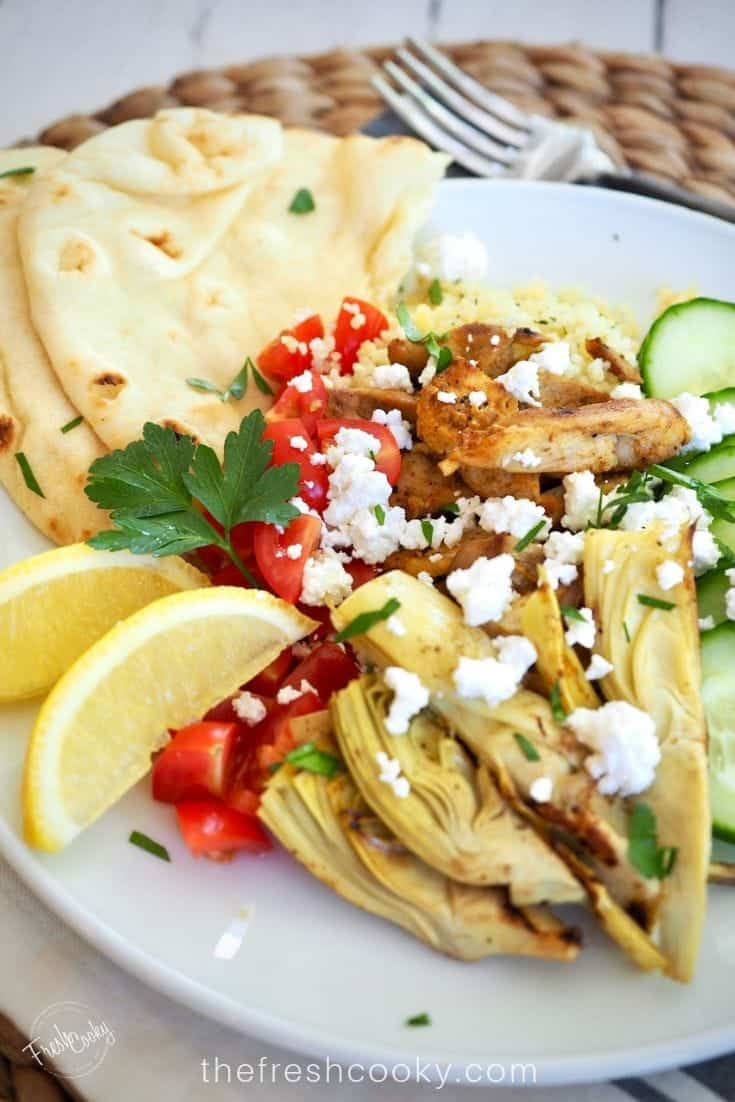 Plate filled with grilled chicken shawarma with artichoke hearts, cucumbers, fresh tomatoes, feta cheese and fresh naan.