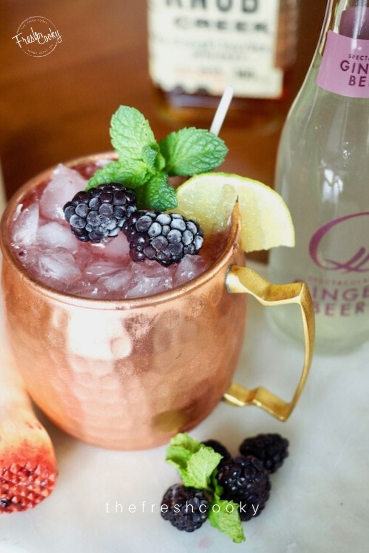 Moscow Mule copper mug filled with a blackberry mule cocktail decorated with mint and a lime and fresh blackberries.