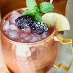 Blackberry Moscow Mule in copper mug with lime, blackberries and mint.