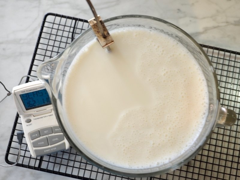 heated milk in glass mixing bowl with temperature probe and digital thermometer cooling.