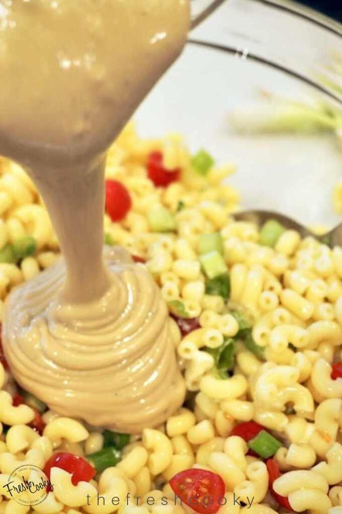 Pouring creamy balsamic ranch vinaigrette onto macaroni salad.