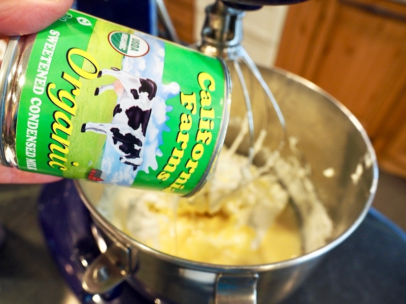 Pouring in organic sweetened condensed milk into whipped cream mixture for Circus Animal Ice Cream.