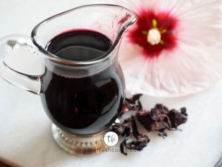 FB image with pitcher of deep red hibiscus simple syrup with dried hibiscus and a fresh hibiscus behind.