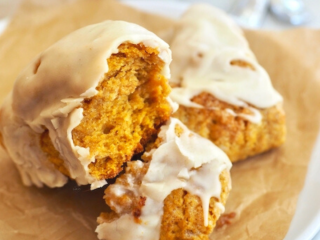 Square image of Pumpkin Scones on a plate, one scone broken in half to reveal a tender, pumpkin spiced center.