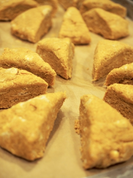 wedges of precooked pumpkin scones on baking sheet with parchment paper
