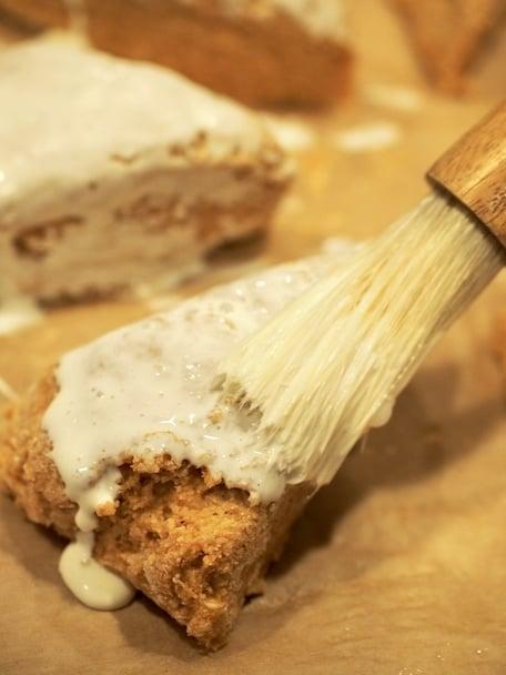 Pastry brush with cream brushing onto uncooked scones on baking sheet.