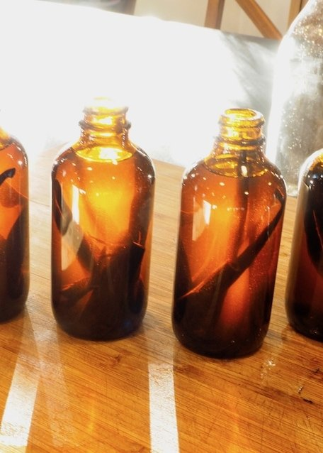 Vanilla in Amber bottles with sunlight from back on cutting board.  | www.thefreshcooky.com