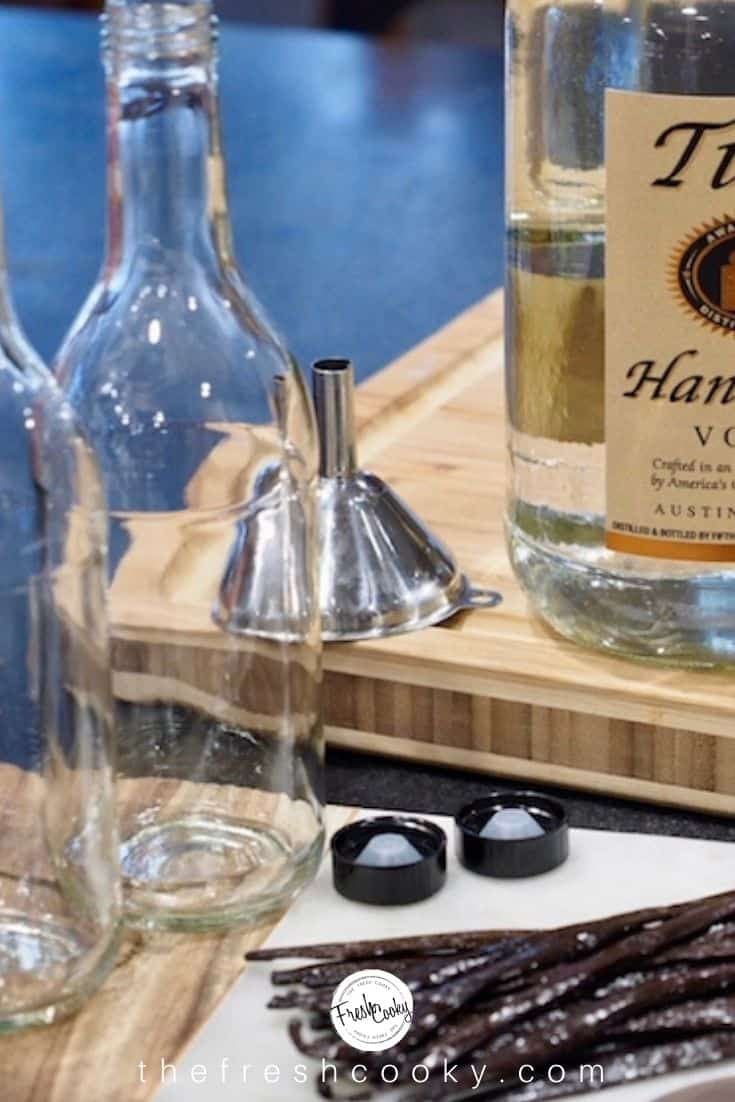two empty glass beverage bottles with lids, a stainless steel funnel and bottle of Titos Vodka with fresh vanilla beans in foreground.
