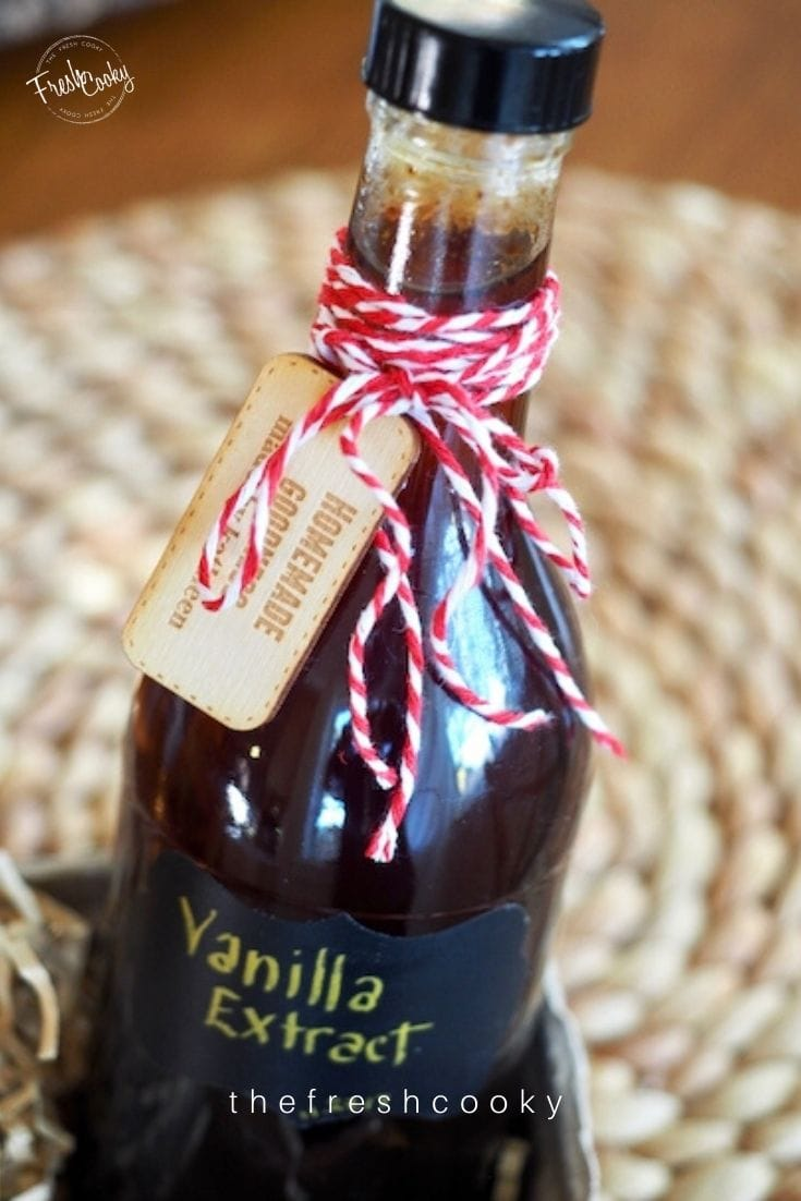 Bottle of vanilla extract with red and white bakers twine tied in bow sitting in a berry box with shreds around it.