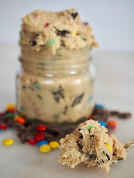 Jar of edible cookie dough with chocolate chips and m&m's spread around, spoonful of cookie dough in foreground.