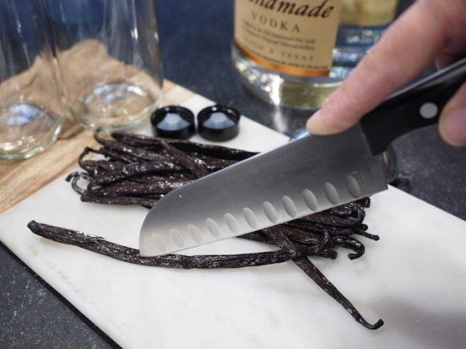 A sharp knife being held with tip in middle of vanilla bean slicing down the middle. Jars and vodka in background. www.thefreshcooky.com