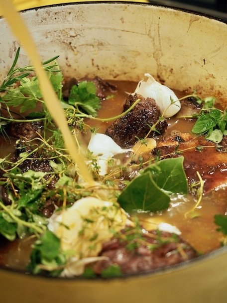 Pouring in beef stock into braised short ribs ready to go into oven in Dutch Oven.