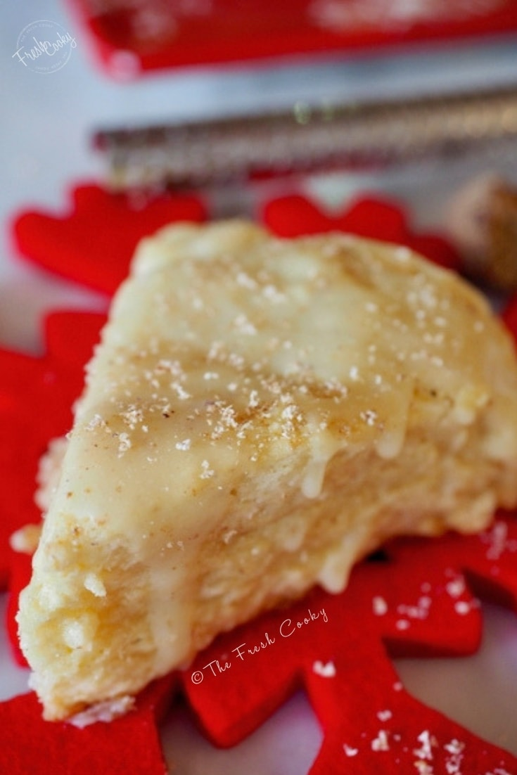 Close up of egg nog scone on red felted wool snowflake with fresh grated nutmeg.