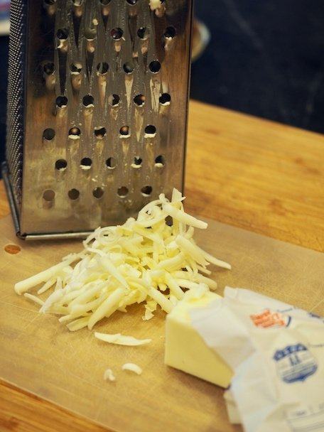 Grated butter on cutting board with box grater in background