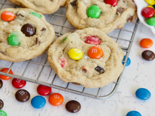 Square image of m & m chocolate cihp cookies on cooling rack with scattered m & m's laying around.