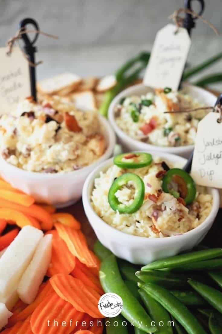 Three different cheese dips in white bowls with veggies surrounding, Jarlsberg Jalapeno, Smoked Gouda and Garlic Gruyere Dip.