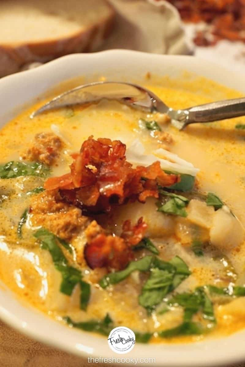 bowl of tuscan soup, with crispy bacon on top and swiss chard on top