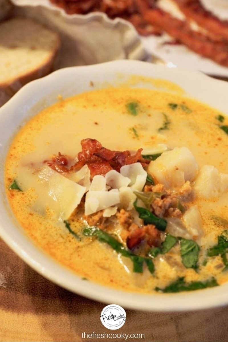 Large white bowl of zuppa toscana, with bacon toppings, sausage, chard in a creamy broth