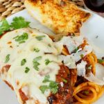 Chicken Parmesan on white plate with spaghetti noodles and slice of garlic toast.