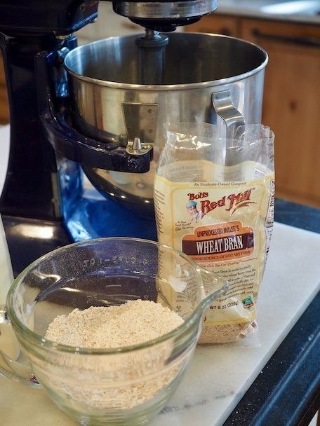 Cobalt Blue mixer in background with bag of wheat bran and mixing bowl with whole wheat flour and bran. | www.thefreshcooky.com
