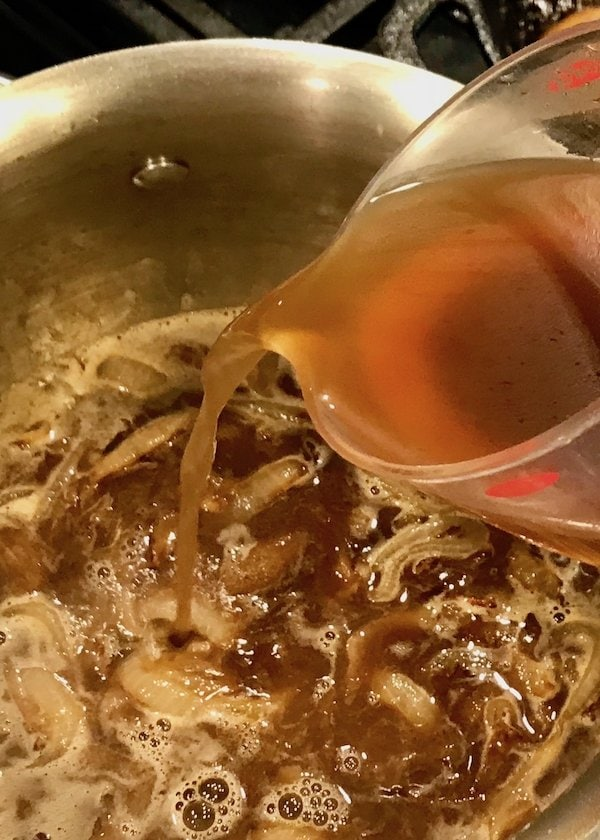 adding beef broth to onion gravy | www.thefreshcooky.com
