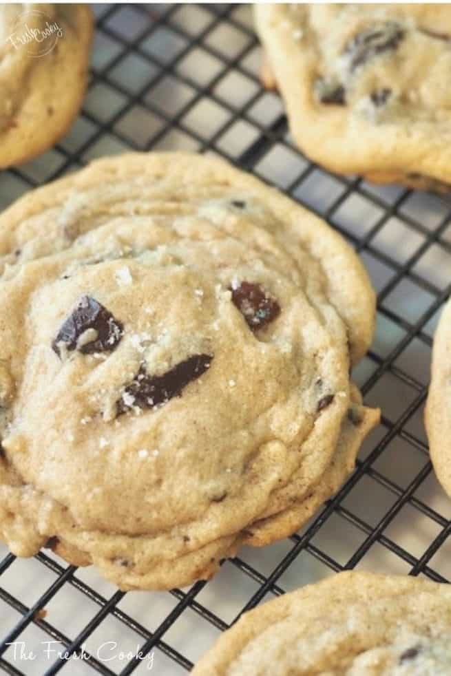 chewy chocolate chip cookies one single cookie on cooling rack with sea salt and chocolate chunks