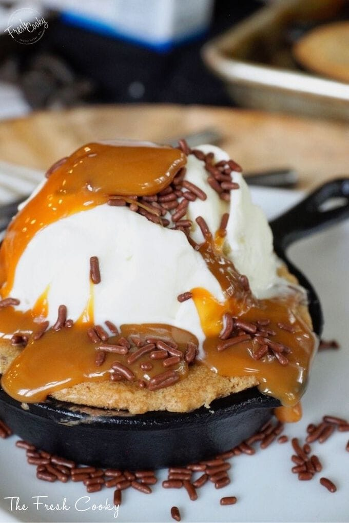 Mini skillet holding a chewy gooey half baked chocolate chip cookie with melting ice cream and caramel and sprinkles.