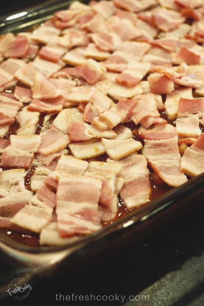 Raw pieces of bacon set on top of baked beans before baking!