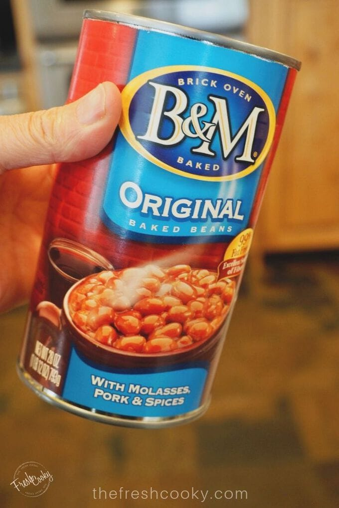 Hand holding large can of B & M baked Beans.