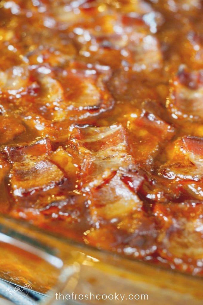 Close up of baked dish of baked beans with crispy bacon on top.