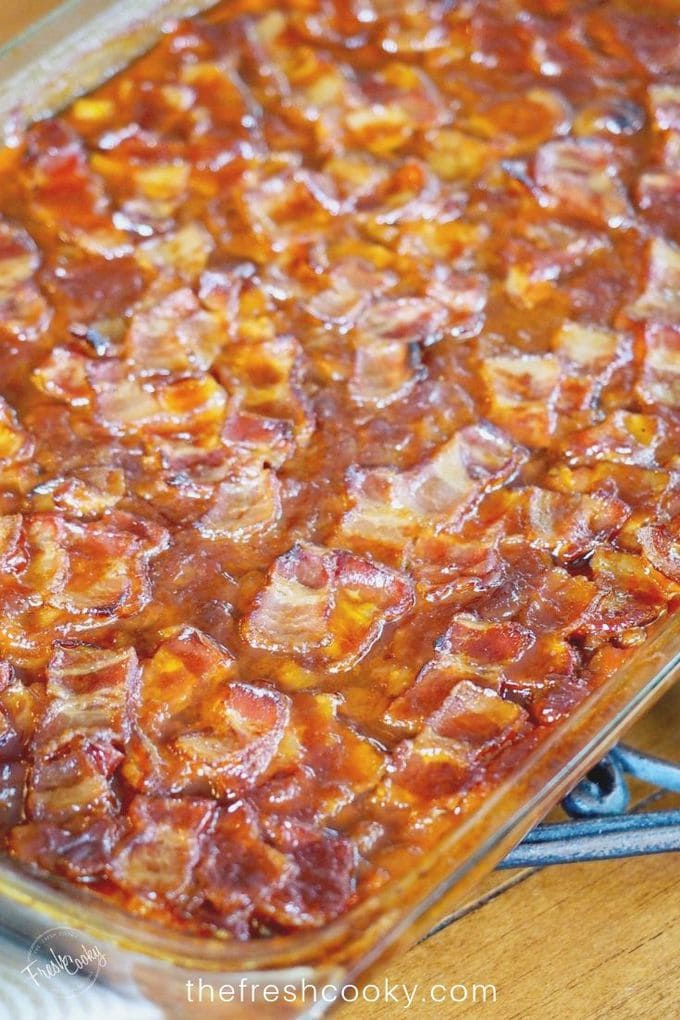 Pin with Pyrex dish filled to the brim with saucy baked beans with crispy bacon on top.