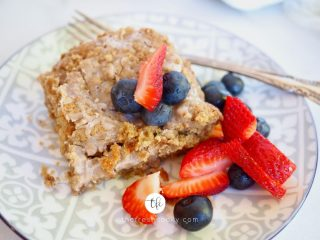 slice of best gluten free coffee cake on decorative plate with mixed berries.