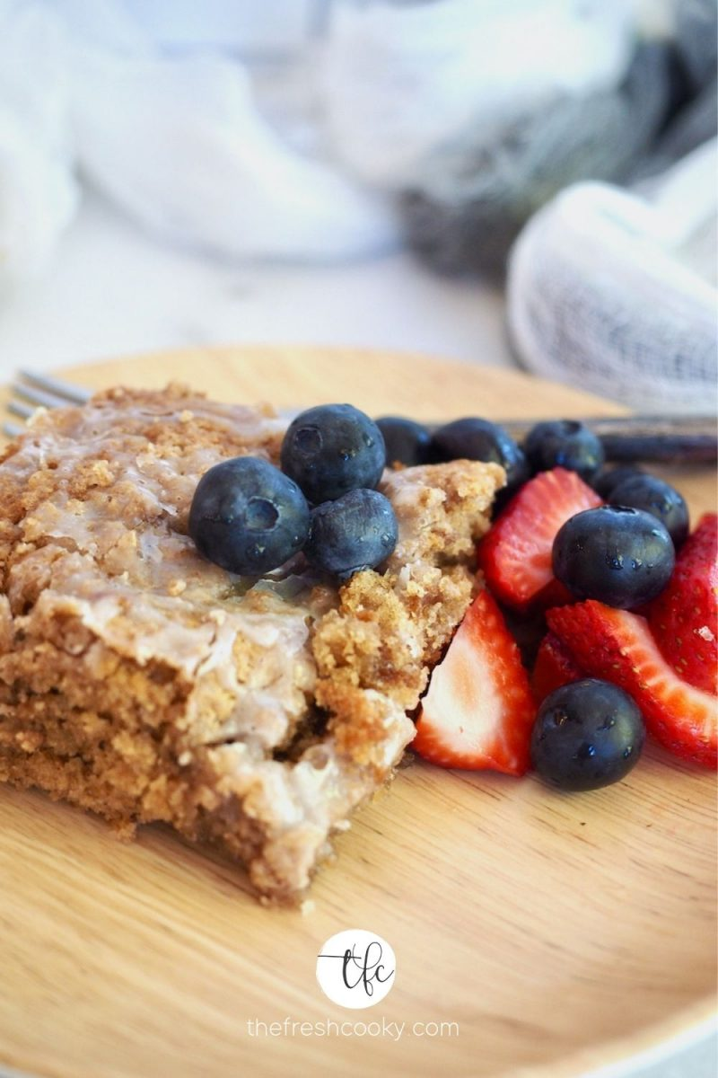Slice of gluten free coffee cake on bamboo plate with blueberries and strawberries.