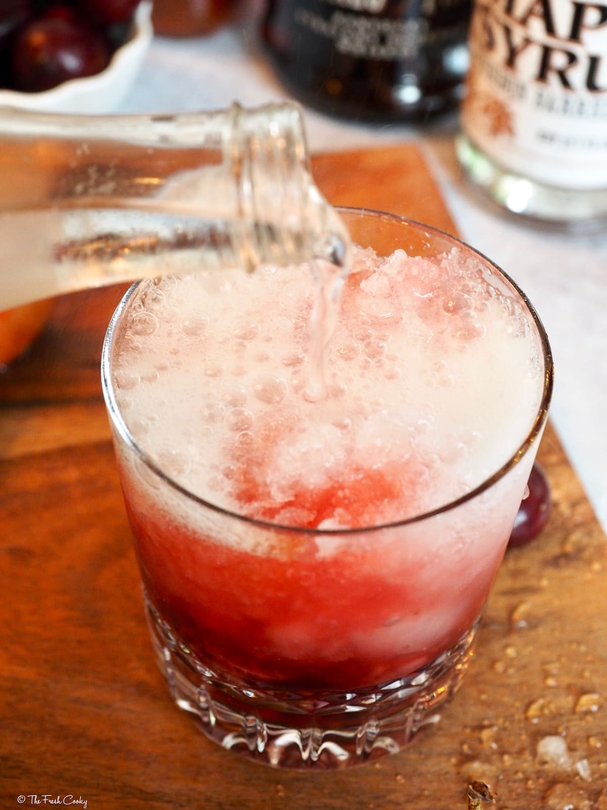 Pouring in a splash of club soda to the Cherry Bomb cocktail.