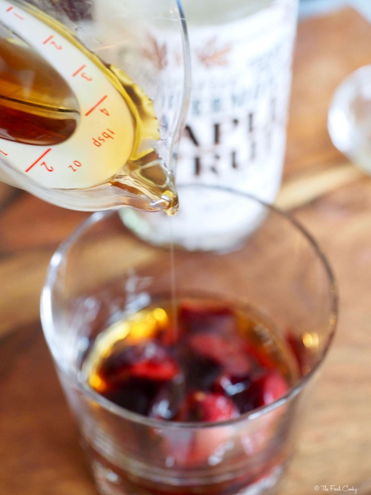 Pouring maple syrup into Cherry Bourbon Cocktail | The Fresh Cooky