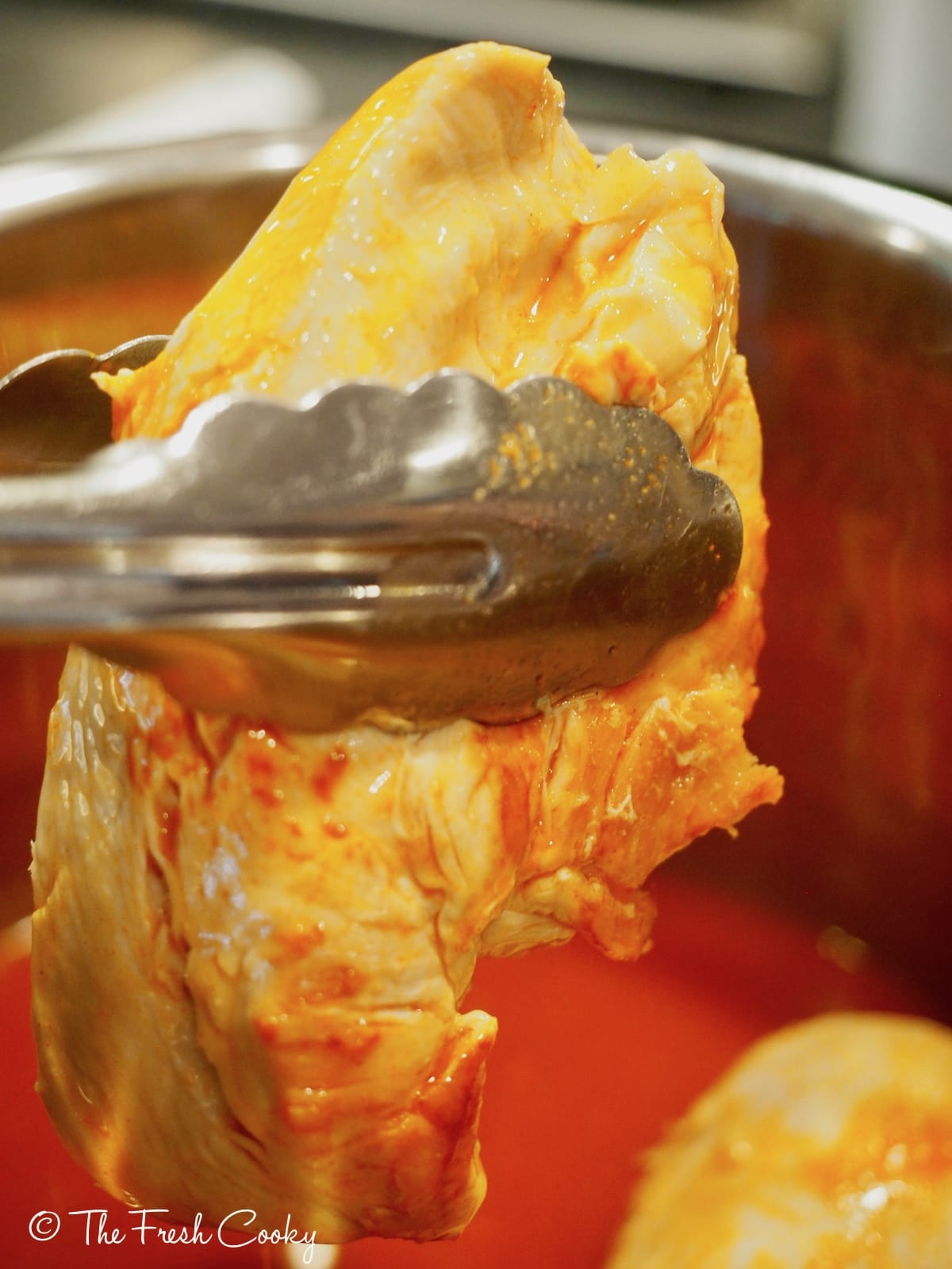 cooked chicken with buffalo wing sauce being pulled out of instant pot. | thefreshcooky.com