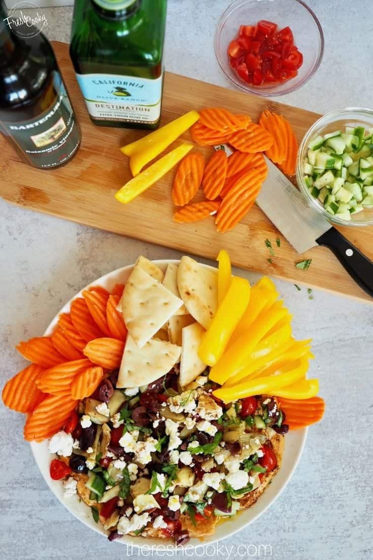 Delicious, fresh mediterranean layered hummus dip with fresh veggies, pita and spices.