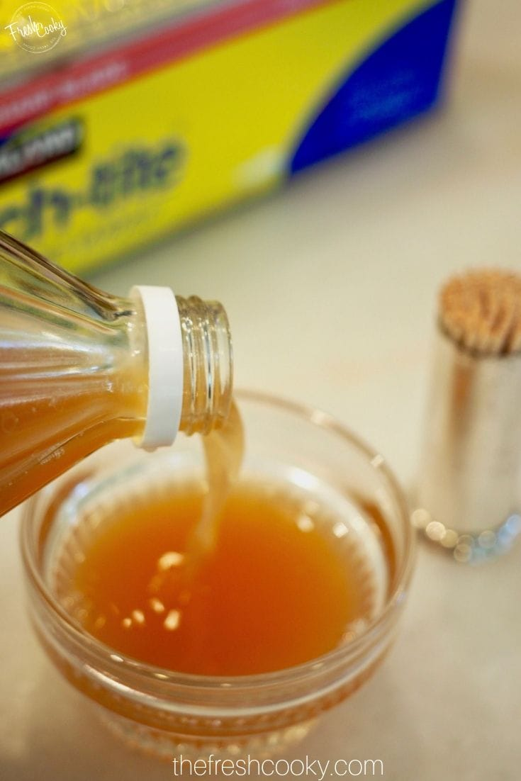 Pouring apple cider vinegar in small glass ramekin for fruit fly trap.