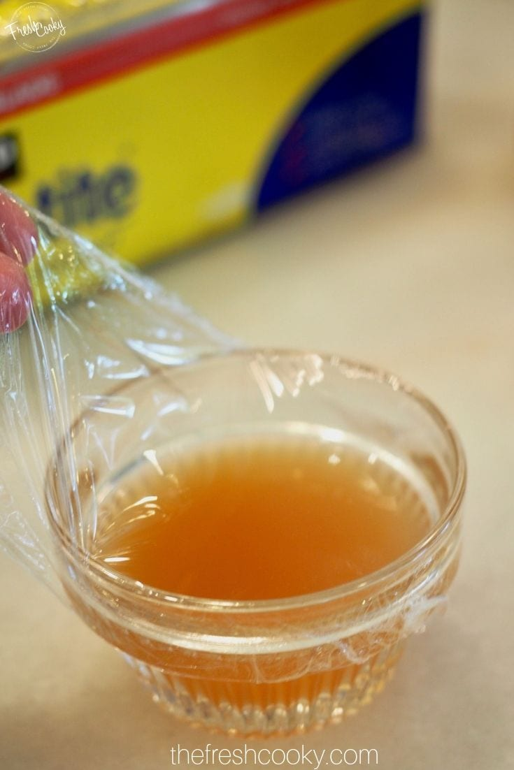 Pulling a piece of plastic wrap tight over the bowl of apple cider vinegar for fruit fly trap.