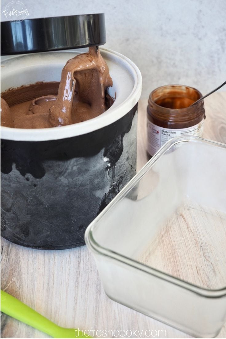 Frozen glass dish with freezer container filled with Chocolate Ice cream and jar of chocolate sauce in background.