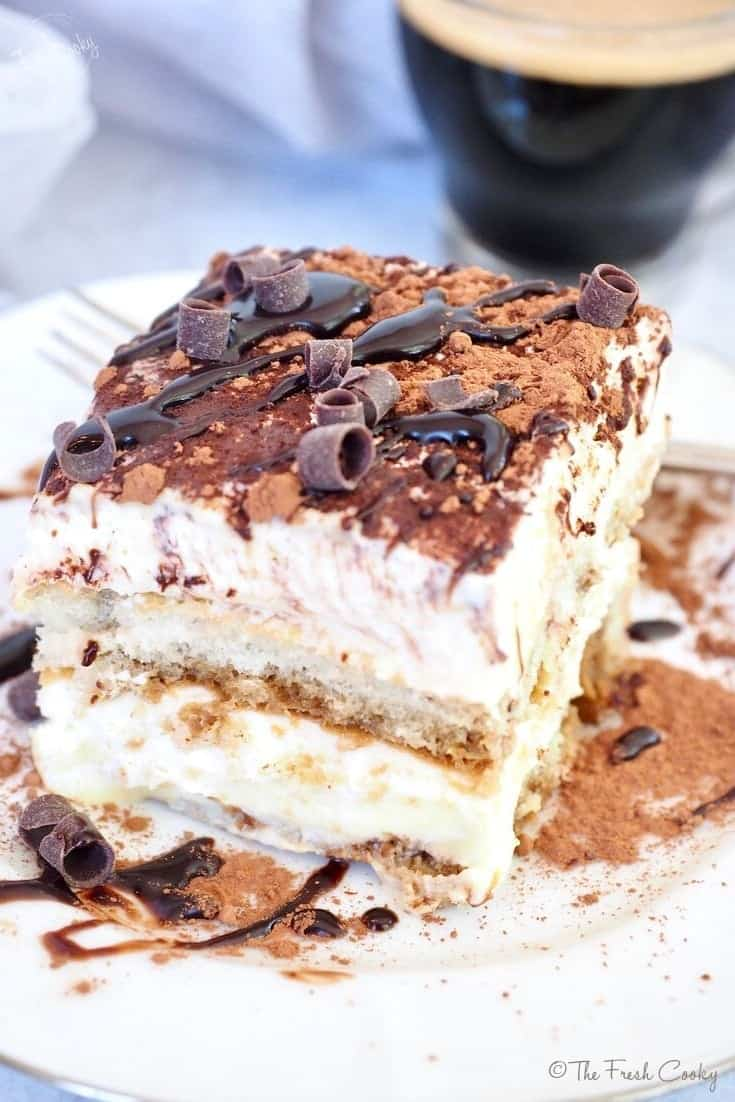 Top shot of a slice of Italian Tiramisu a layered custard dessert with ladyfingers, custard and whipped cream, topped with cocoa powder, chocolate curls and a drizzles of chocolate sauce. with a small cup of espresso along with it. Recipe via @thefreshcooky