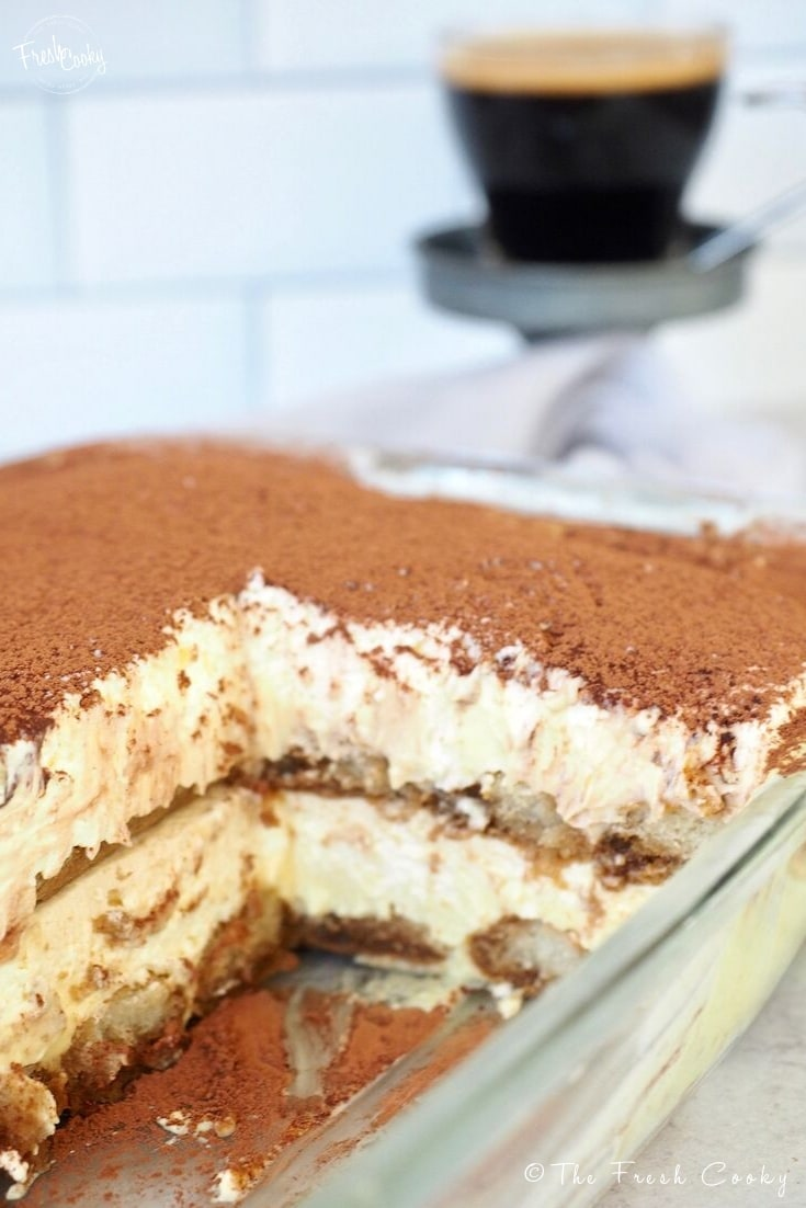 Pan of layered tiramisu with section pulled out. Delicious layers of ladyfingers soaked in espresso and rum between custard and whipped cream layers, dusted with cocoa powder. Recipe via @thefreshcooky