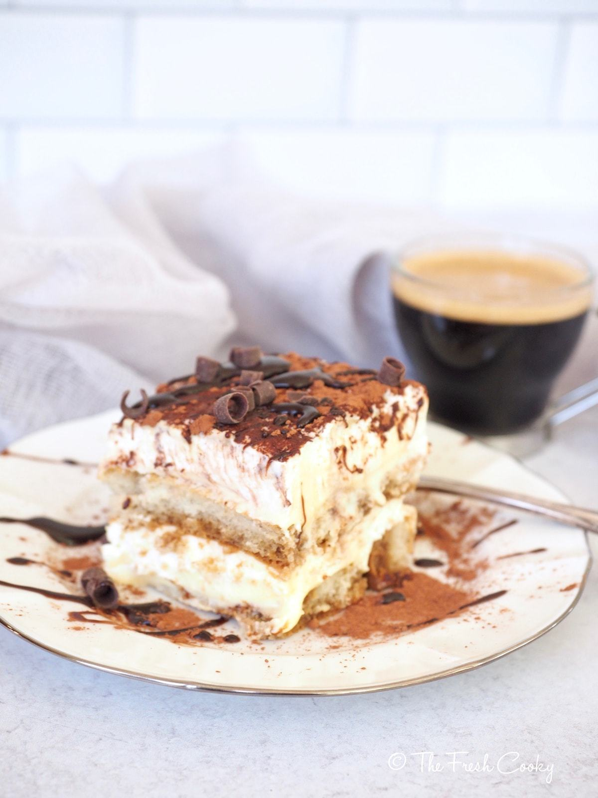 A plate with a slice of Italian layered Tiramisu with a shot of Espresso in the background
