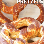 Long pin with image of two giant bavarian pretzels on a wooden platter.