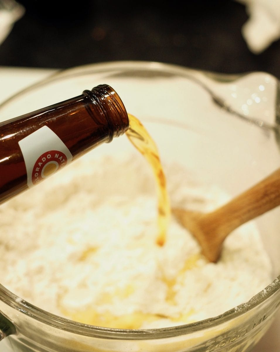 pouring beer in dry ingredients for cheddar beer popovers | thefreshcooky.com