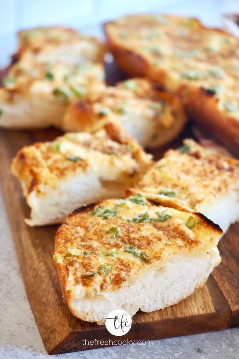 Sliced pieces of cheesy garlic bread on cutting board.