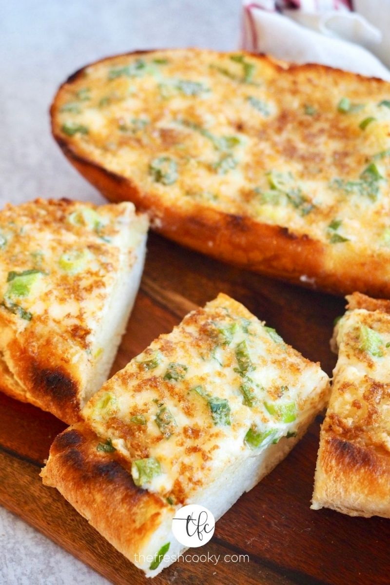 Image of cheesey garlic bread on cutting board with half loaf and several slices in forefront.