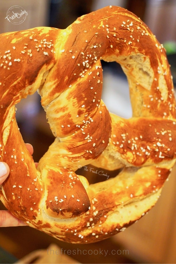 Holding up a giant, baked German Pretzel | thefreshcooky.com