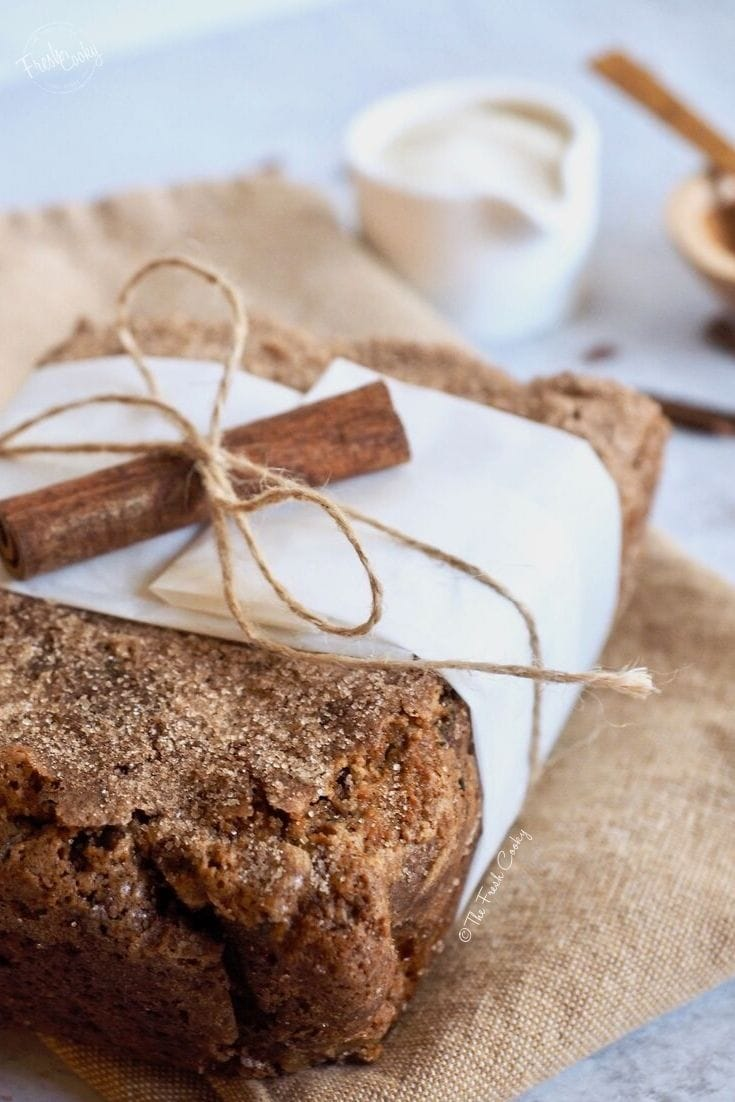 half loaf of snickerdoodle zucchini bread tied with string, parchment and a cinnamon stick. | thefreshcooky.com