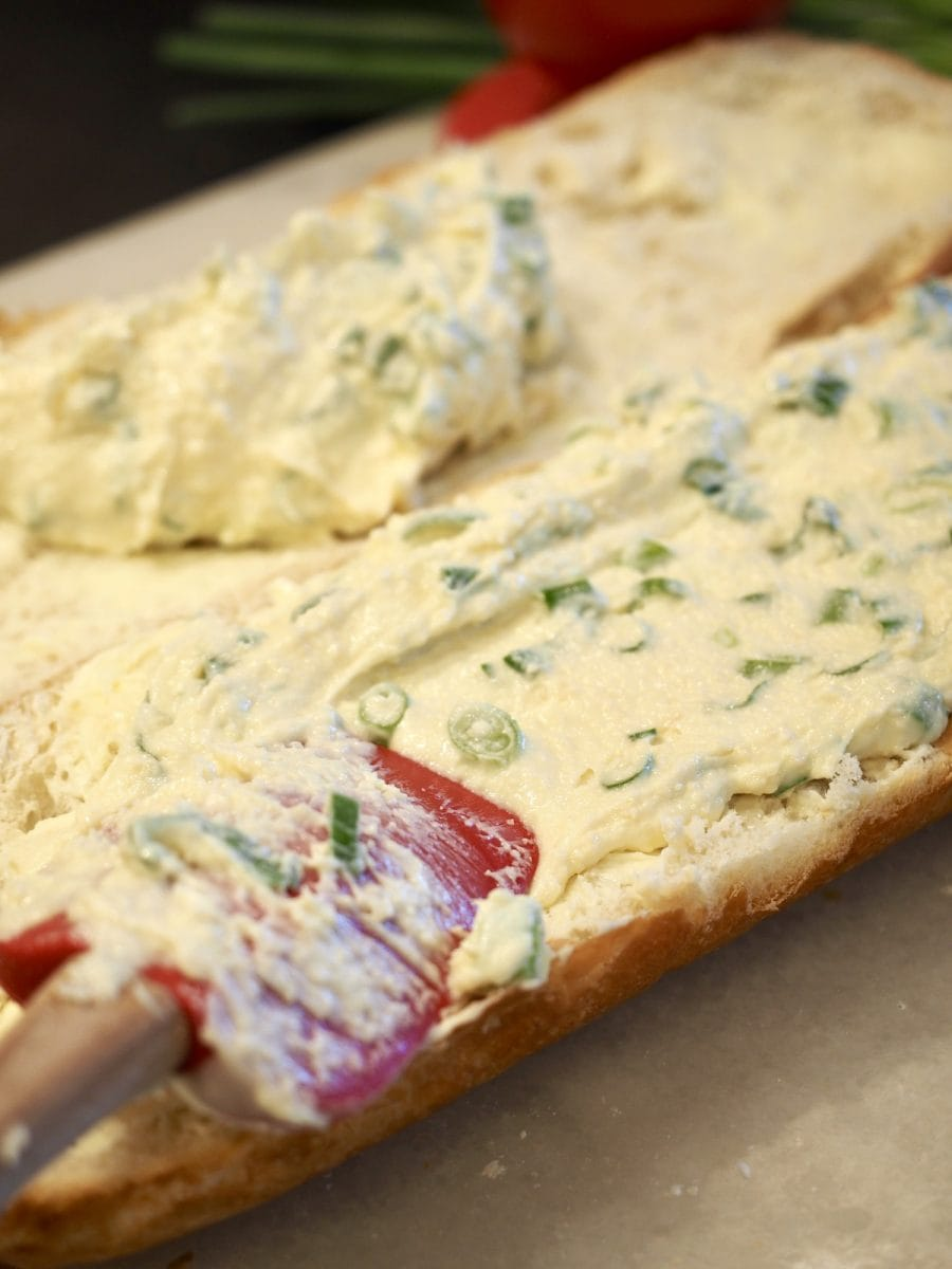 spreading cheesy spread on french bread | thefreshcooky.com